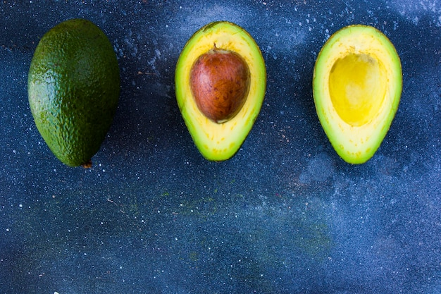 Meio abacate na mesa azul, vegetais e frutas