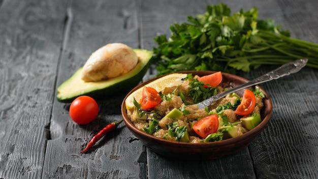 Meio abacate, pimentão, tomate e uma tigela de salada em uma mesa de madeira escura.