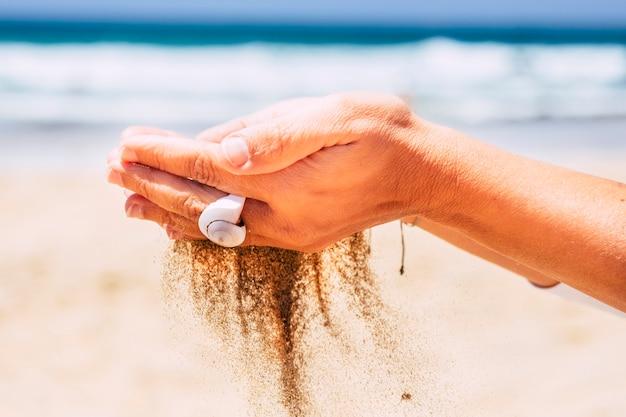 Meio ambiente e respeito pela natureza com mãos de mulher pegando areia caindo