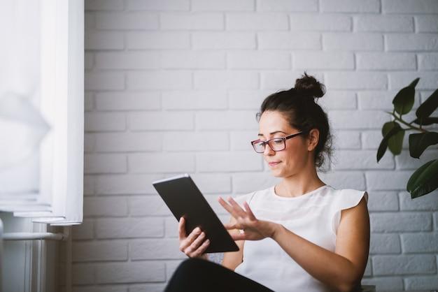 Meio atraente mulher atraente olhando tablet pesquisando on-line.