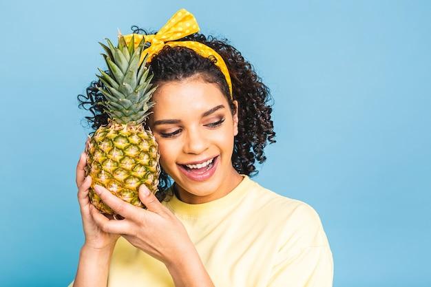 Meio-campista exótico de abacaxi em uma dieta. a garota alegre de pele escura negra afro-americana tem nas mãos o abacaxi isolado sobre fundo azul.