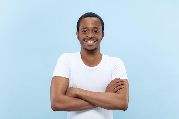 Meio comprimento close-up retrato de jovem afro-americano em camisa branca no espaço azul