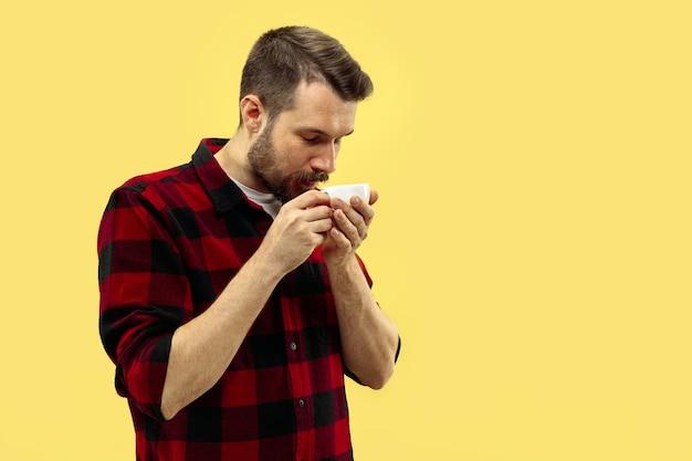 Meio comprimento close-up retrato de jovem em camisa no espaço amarelo