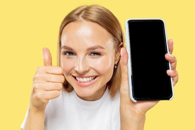 Meio comprimento do retrato de mulher jovem caucasiana em fundo amarelo do estúdio. bela modelo feminino em camisa branca. conceito de emoções, expressão facial, vendas, pagamento online. mostrando a tela do telefone.
