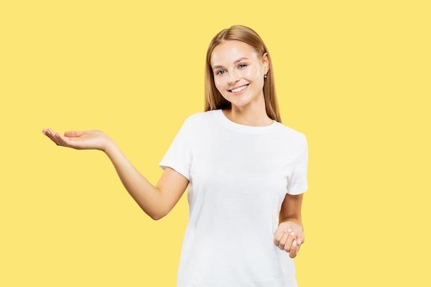 Meio comprimento do retrato de mulher jovem caucasiana em fundo amarelo do estúdio. bela modelo feminino em camisa branca. conceito de emoções humanas, expressão facial. mostrando e apontando algo.