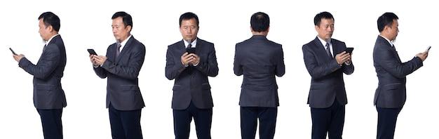 Meio corpo de colagem de 50s 60s asiáticos idosos homem negócios ternos óculos e sapatos. o gerente sênior usa a rede social do telefone inteligente e gira 360 a vista traseira lateral sobre o fundo branco isolado