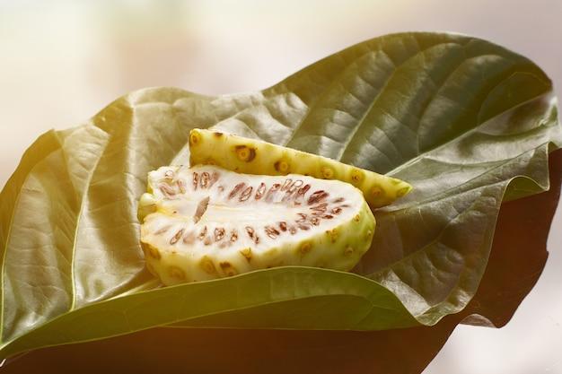 Meio corte de frutas noni frescas