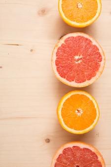 Meio corte laranja e toranja plana leigos na madeira