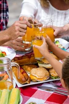 Meio da família brindando bebidas enquanto almoça