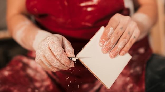 Meio da mão do oleiro feminino removendo a tinta na borda da telha
