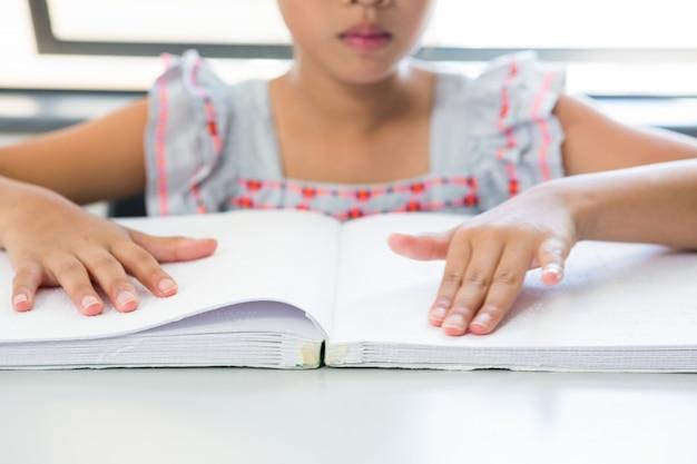 Meio da menina cega lendo o livro em braille