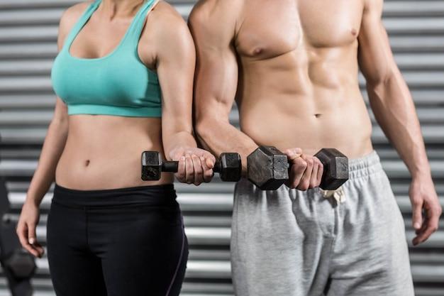 Meio de ajuste casal levantando halteres no ginásio