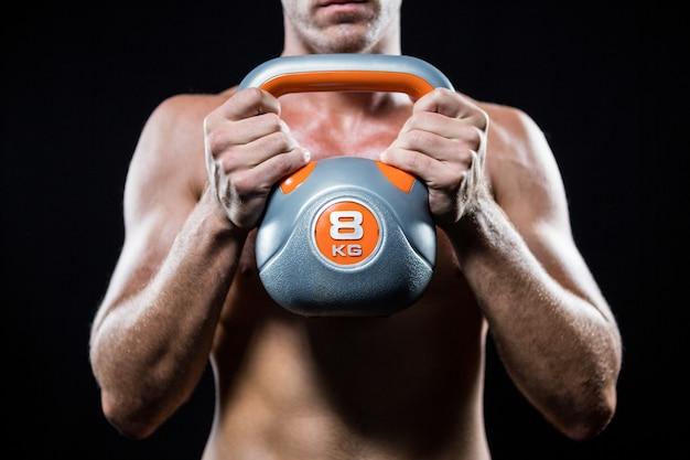 Meio de atleta sem camisa, segurando o kettlebell