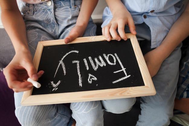 Meio de crianças segurando o giz e ardósia com texto de família