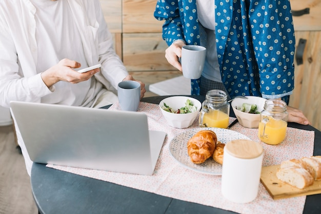Meio de homens segurando a xícara de café perto delicioso café da manhã com suco e laptop sobre a mesa de madeira