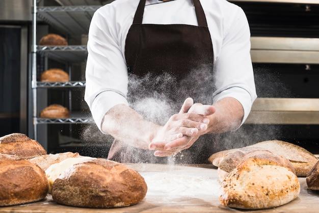 Meio de mão de um padeiro masculino polvilhando a farinha na mesa de madeira com pão assado