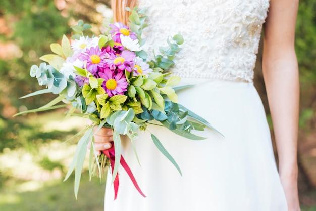 Meio de mão de uma noiva segurando buquê de flores