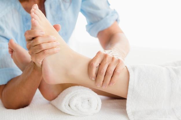 Meio de massagista dando massagem nos pés para mulher