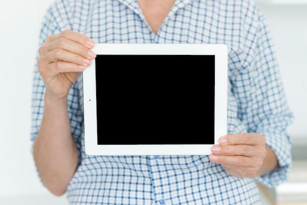 Meio de mulher mostrando tablet digital com tela em branco