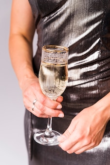 Meio de mulher segurando a taça de champanhe