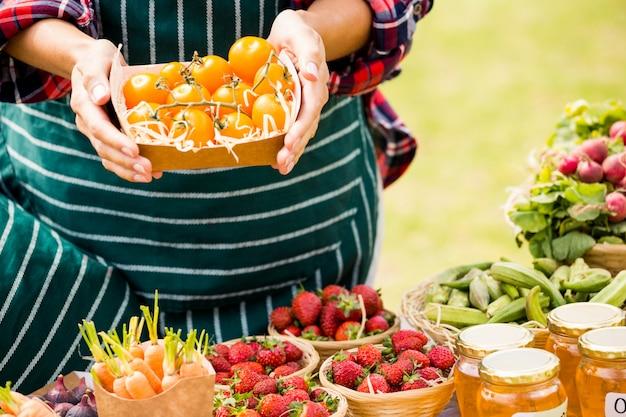 Meio de mulher segurando tomates em caixa