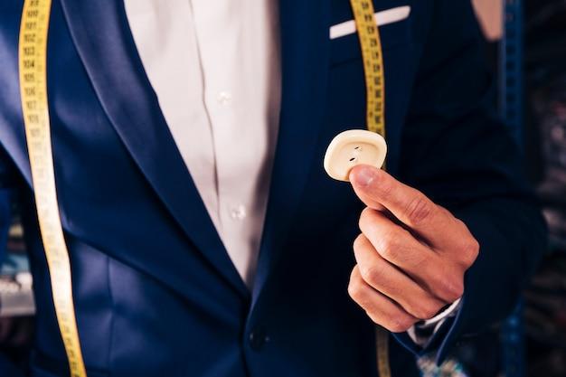 Meio de um alfaiate masculino, mostrando o botão branco