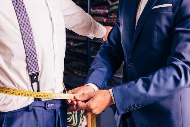 Meio de um alfaiate masculino que toma a medida da cintura do homem