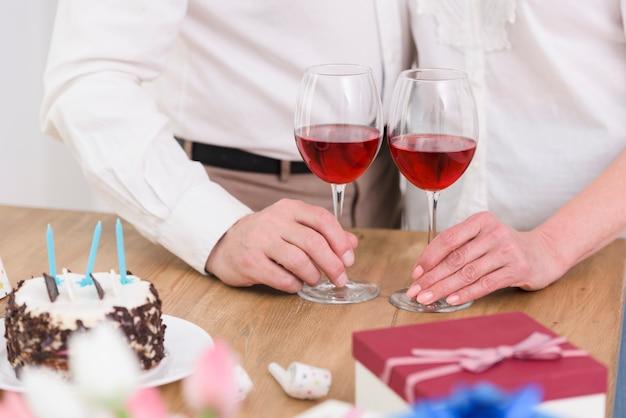 Meio de um casal em pé perto da mesa com taças de vinho; bolo de aniversário e caixa de presente