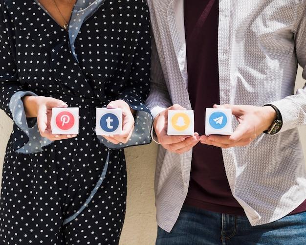 Meio de um casal segurando caixas de ícones de mídia social