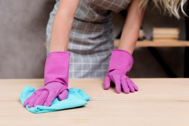 Meio de um faxineiro feminino, limpando a mesa de madeira com pano