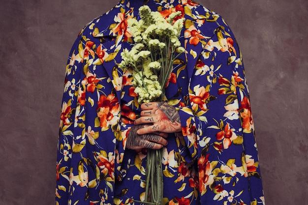 Meio de um homem com tatuagem na mão segurando flor limonium amarela