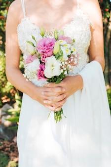 Meio de uma noiva de vestido branco, segurando o buquê de flores nas mãos dela