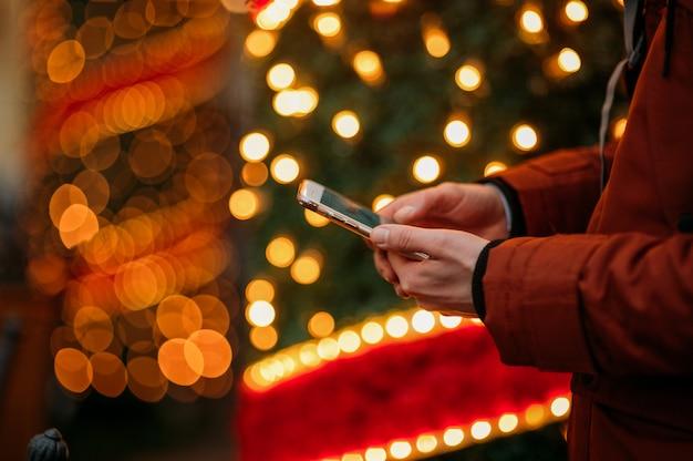 Meio do homem que usa o telefone inteligente contra a árvore de natal iluminada.