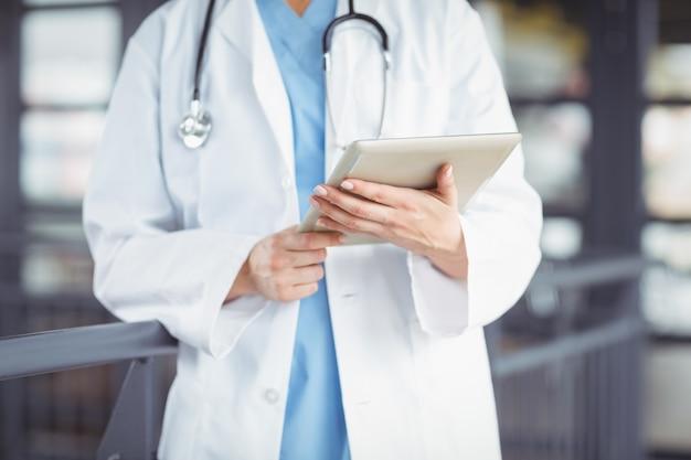Meio do médico segurando o tablet digital
