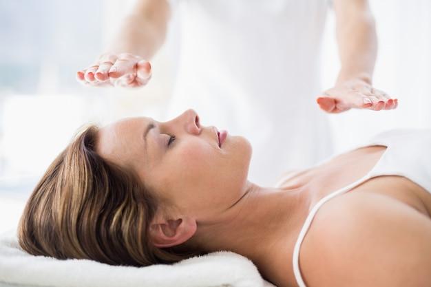 Meio do terapeuta realizando tratamento de reiki na mulher