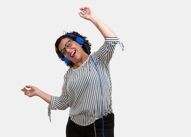 Meio envelheceu mulher escutar música, dançar e se divertir, em movimento