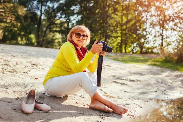 Meio envelheceu, mulher, verificar, imagens, ligado, câmera, sentando, por, outono, rio, banco