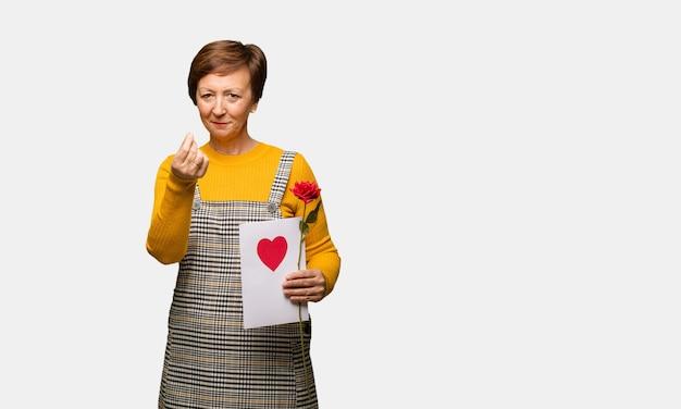Meio envelhecida mulher comemorando o dia dos namorados, fazendo um gesto de necessidade