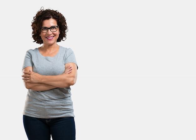 Meio envelhecida mulher cruzando os braços, sorrindo e feliz, sendo confiante e amigável