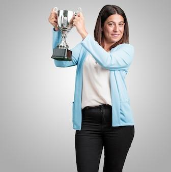 Meio envelhecida mulher excitada e enérgica, levantando um copo depois de ter conseguido uma vitória difícil, recompensa por trabalho árduo, confiante e positivo