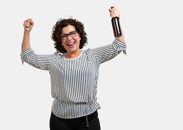 Meio envelhecida mulher feliz e divertida, segurando uma garrafa de cerveja, se sente bem depois de um dia intenso