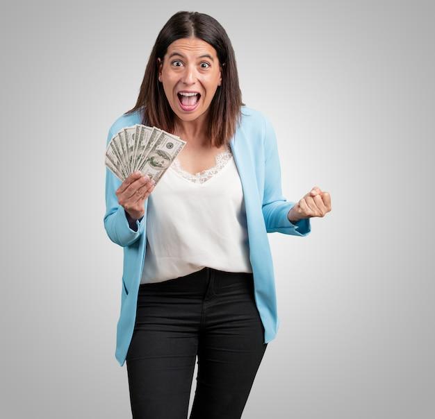 Meio envelhecida mulher muito animada e eufórica, gritando olhando para a frente, comemorando uma vitória e sucesso tendo ganho na loteria, segurando as notas com a mão, conceito de sorte