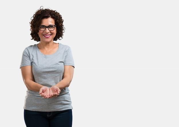 Meio envelhecida mulher segurando algo com as mãos, mostrando um produto