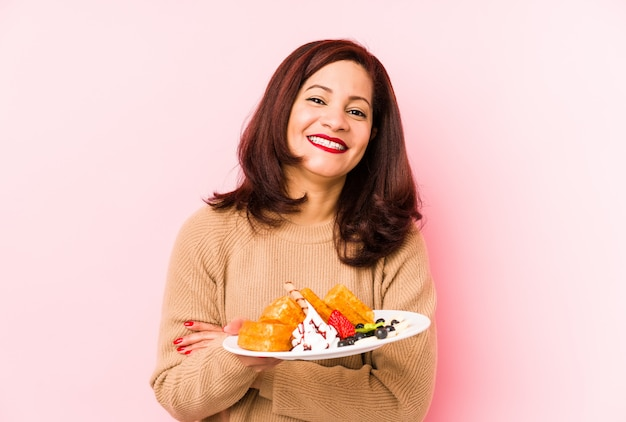 Meio envelhecida mulher segurando um waffle rindo e se divertindo