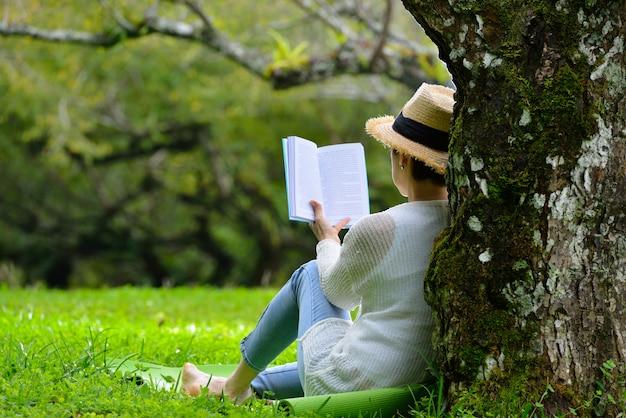 Meio envelhecida mulher sentada debaixo de uma árvore, lendo um livro no parque