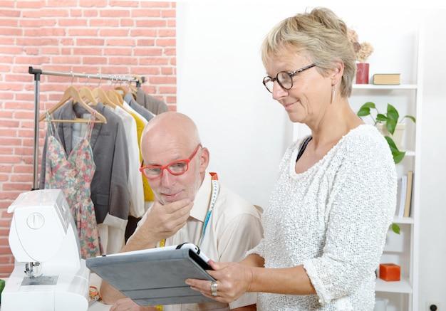 Meio envelhecido casal em uma oficina de costura