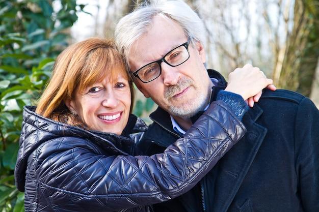 Meio envelhecido casal fofo abraçando ao ar livre