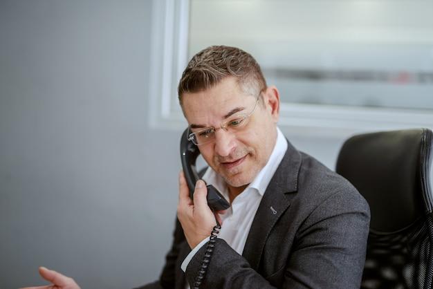 Meio envelhecido empresário com roupa formal, tendo um telefone falar enquanto está sentado em seu escritório. algumas pessoas obtêm sucesso porque estão destinadas a fazê-lo, mas a maioria tem sucesso porque está determinada a fazê-lo.