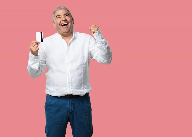Meio envelhecido homem alegre e sorridente, muito animado, segurando o novo cartão de banco, pronto para ir às compras