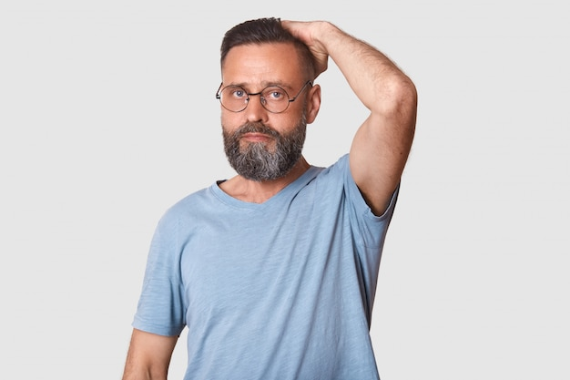 Meio envelhecido homem barbudo bonito com óculos elegantes vestindo luz azul camiseta casual. modelo de trabalho duro coloca isolado na luz.